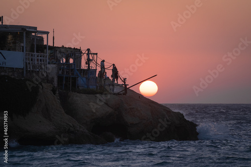 Canvas Print Tranquil scenery of the silhouette of a fisherman's boathouse on the cliff at ru
