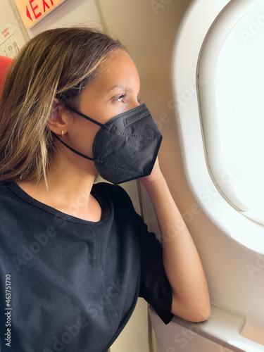 Traveler in mask in plane cabin