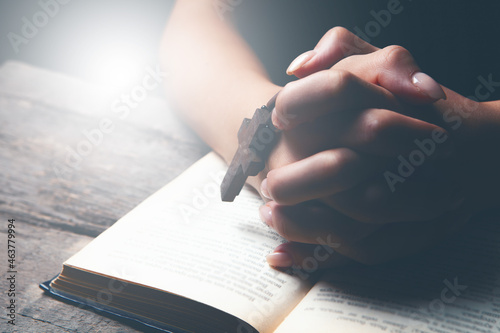 Fototapeta woman praying on book holding cross