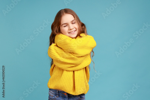 Fototapeta Portrait of charming little girl embracing herself and smiling from happiness, positive self-esteem, wearing yellow casual style sweater