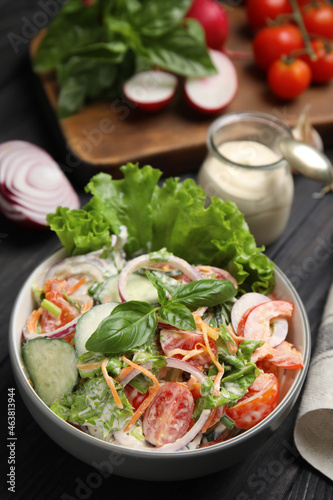 Bowl of delicious vegetable salad dressed with mayonnaise and ingredients on black table