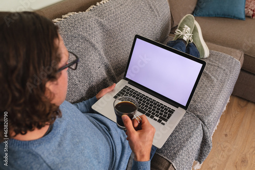 Rear view of disabled man holding coffee cup using laptop with copy space on couch at home