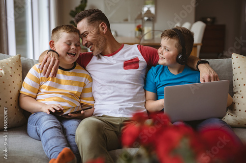 Portrait of caucasian father and two sons with laptop and digital tablet smiling at home