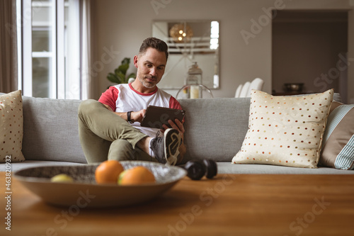 Caucasian man using digital tablet sitting on the couch at home