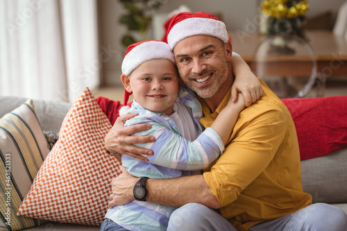 Portrait of caucasian father and son hugging and smiling at home during christmas