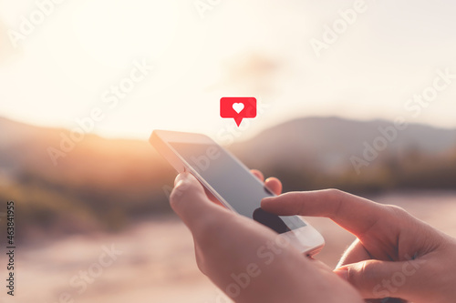 Obraz na plátně Close up woman hand hold using smart phone with heart icon at top of mountain and sunset sky background