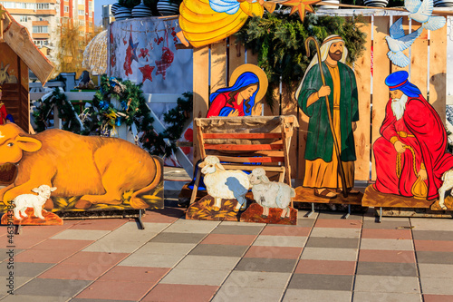 Fotografie, Obraz Wooden Christmas Nativity scene with Holy family in city park