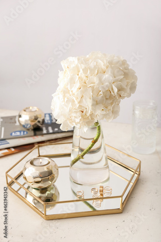 Beautiful hydrangea in glass vase and stylish decor on table in interior of light room