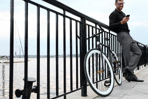 Valokuva Businessman with bicycle on embankment