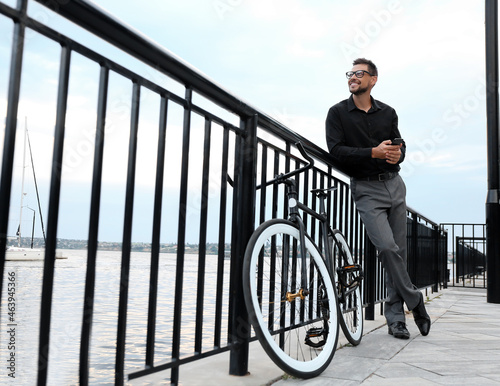 Canvas-taulu Businessman with bicycle on embankment