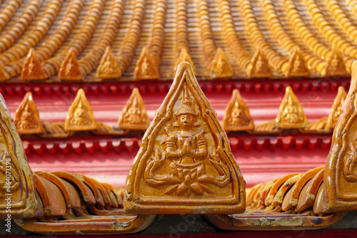 Murais de parede Close-up of traditional Thai roof tile in orange color with Buddhist gods carved