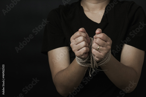 Murais de parede Slave Asian woman fears she was hands tied up with rope black background