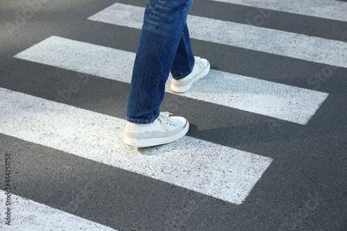 Man in jeans and sneakers walking on crosswalk Fotobehang