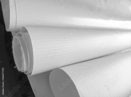 rolls of plain white striped flexion material on a dark background Fotobehang