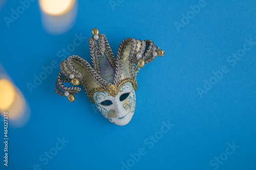 Obraz na plátne Top view of venetian carnival mask and lights on the blue background