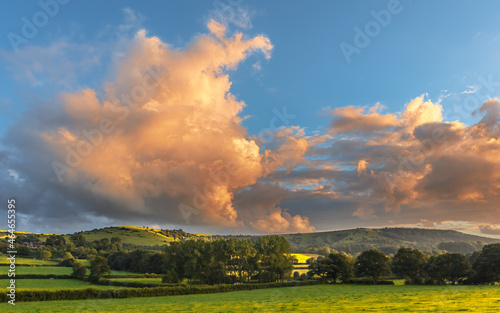 Canvas Print Beautiful view of large clouds over a green hillside meadow